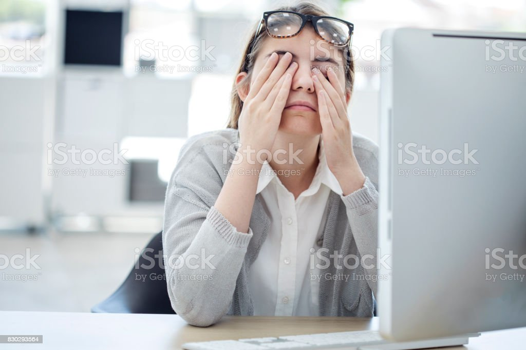 Tired woman touching her eyes stock photo