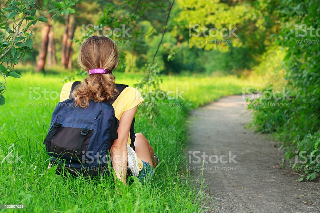 Tired woman traveler sitting on the grass royalty-free stock photo
