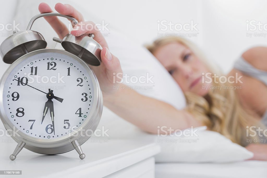 Tired woman turning off the alarm clock royalty-free stock photo