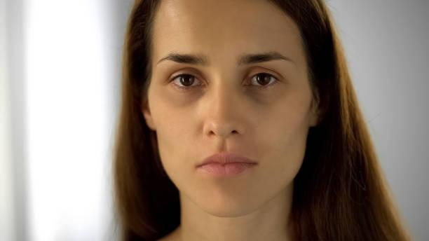 mujer cansada con círculos negros bajo los ojos mirando a cámara, la falta de sueño - human trafficking fotografías e imágenes de stock