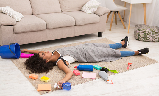 istock Tired woman with cleaning supplies lying on floor 1080849780