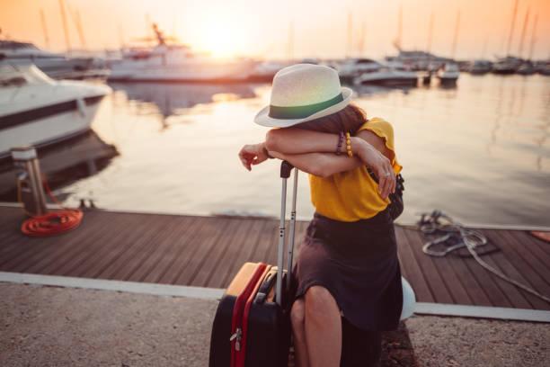 tired woman with suitcase at the marina - donna valigia solitudine foto e immagini stock