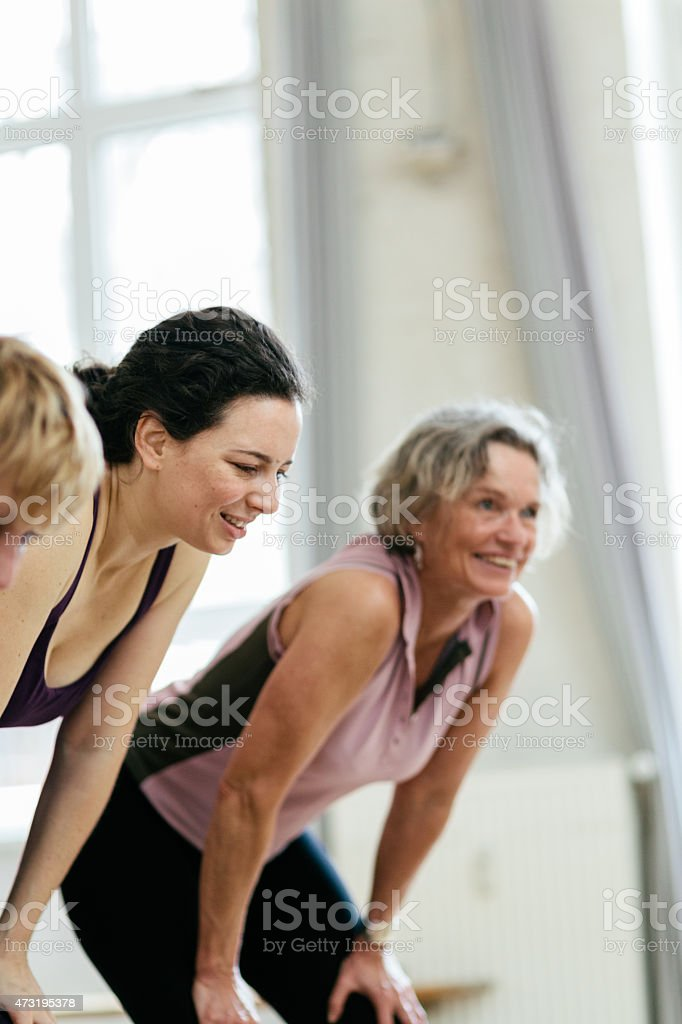 Tired women with hands on knees smiling in gym stock photo