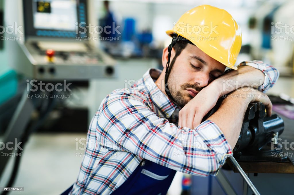 Tired worker fall asleep during working hours in factory stock photo