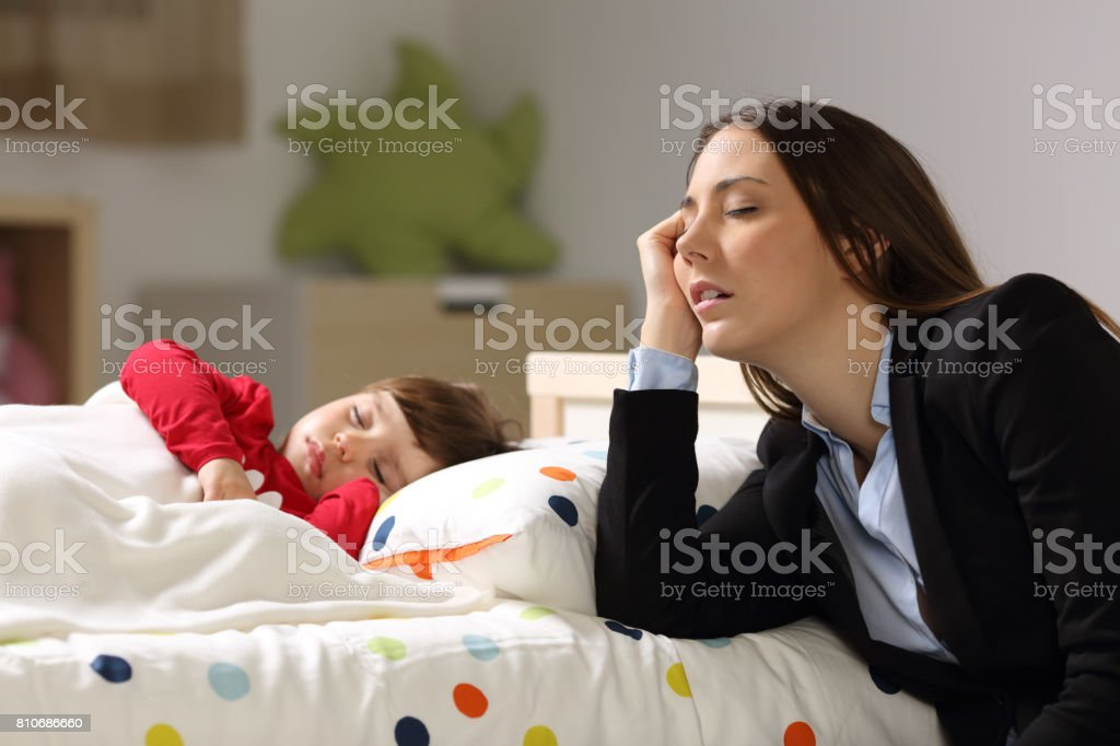 Tired worker mother sleeping beside her daughter stock photo