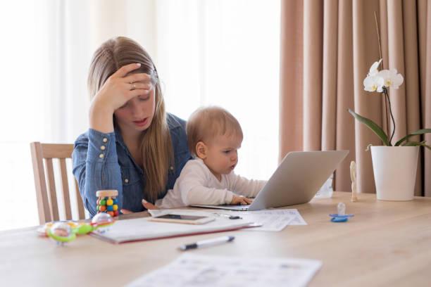 moe werkende moeder met kind in haar schoot uitgeput gevoel - snavel stockfoto's en -beelden
