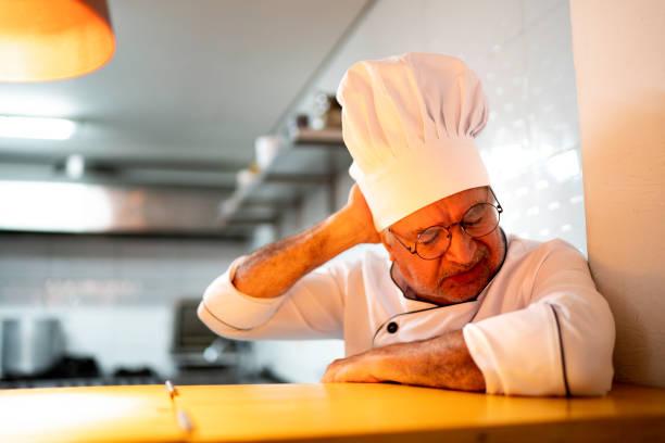 a tired / worried senior chef in the kitchen counter - chef triste foto e immagini stock