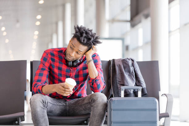 Tired young african waiting for flight in airport lounge Bored young african man sitting on chair with suitcase in airport lounge and waiting for flight. jet lag stock pictures, royalty-free photos & images