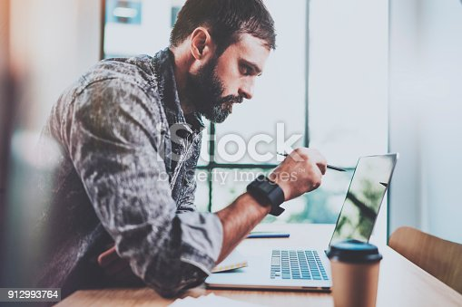 istock Tired young bearded man making pause after hard work day.Coworker working process at sunny office.Horizontal.Blurred background. 912993764