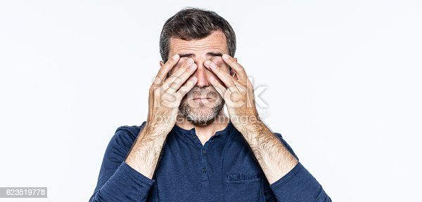 istock tired young bearded man massaging his sleeping eyes from burnout 623519778