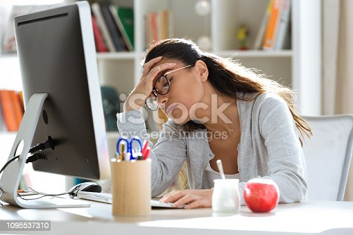 istock Tired young business woman having headache while working with computer in the office. 1095537310