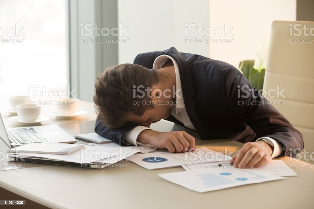 Tired young businessman sleeping on desk in office stock photo