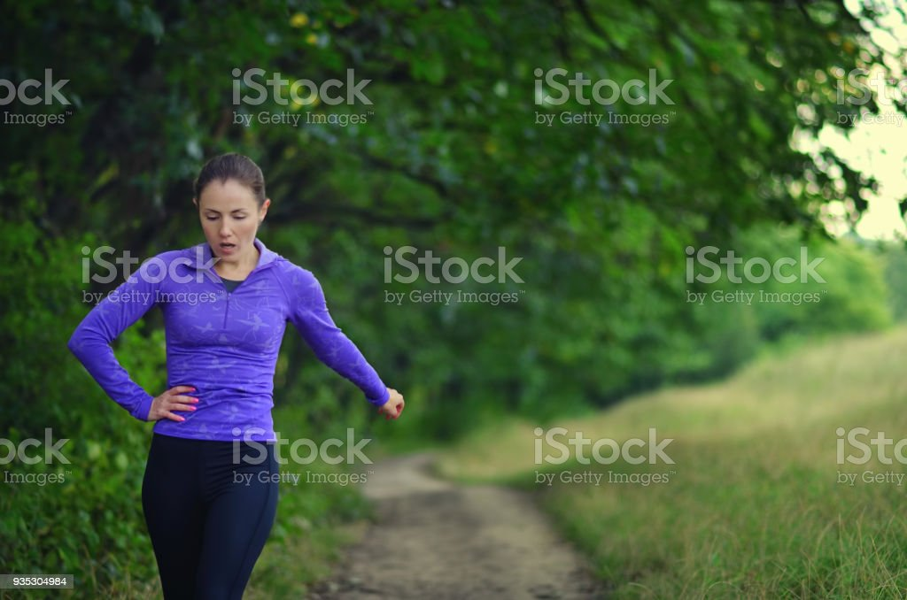 Tired young girl on a run in the forest. stock photo