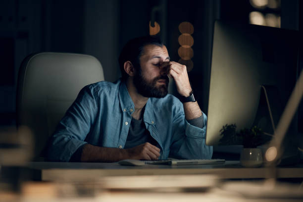 Tired young hipster computer programmer in casual shirt sitting at table and rubbing bridge of nose while working late in office stock photo