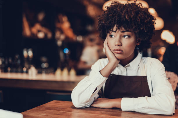 Tired young lady looking aside and sitting over table stock photo