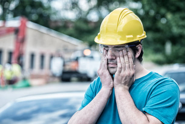 Tired Young Man Blue Collar Construction Worker Rubbing His Eyes stock photo
