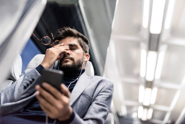 Tired young man having a headache while listening to podcasts in the train. stock photo