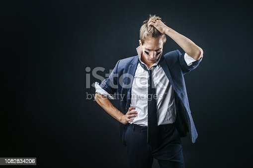 istock Tired young man in a business suit rolled up his sleeves. Businessman with war paint 1082834206