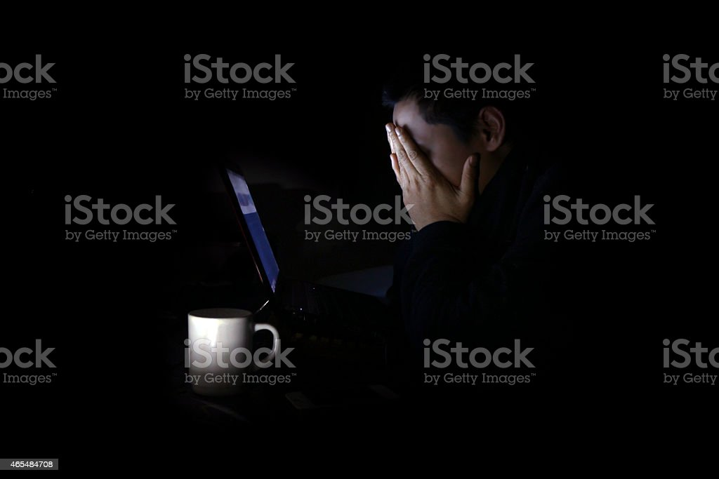 Tired young man on his laptop at night stock photo