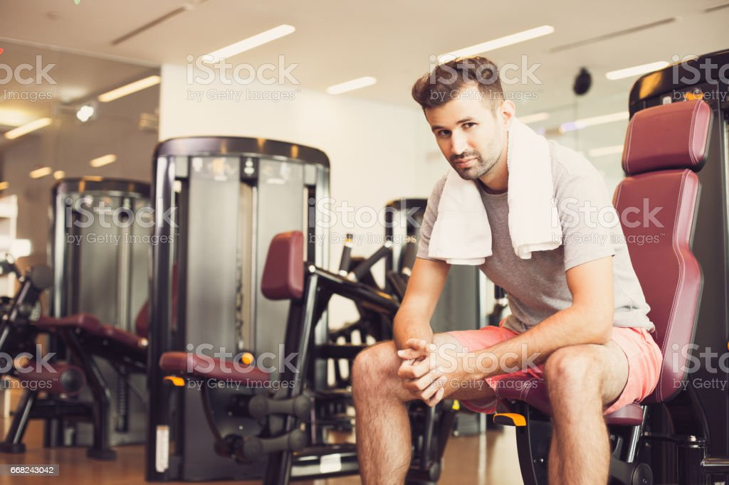 Tired young man relaxing on weight machine in gym foto stock royalty-free