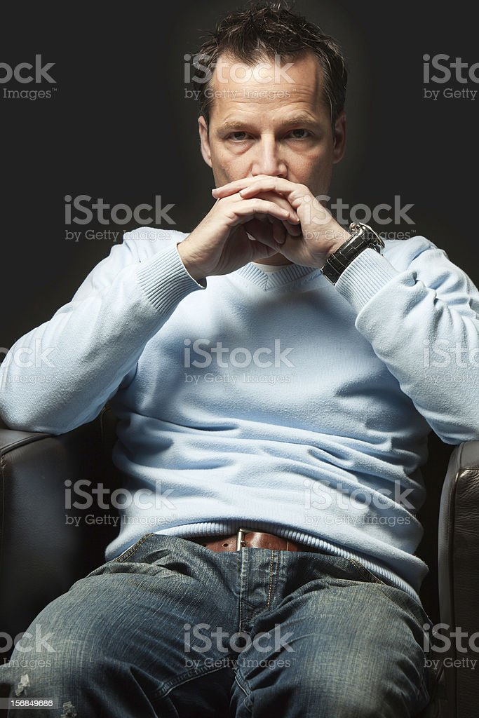 Tired young man sitting in arm chair stock photo