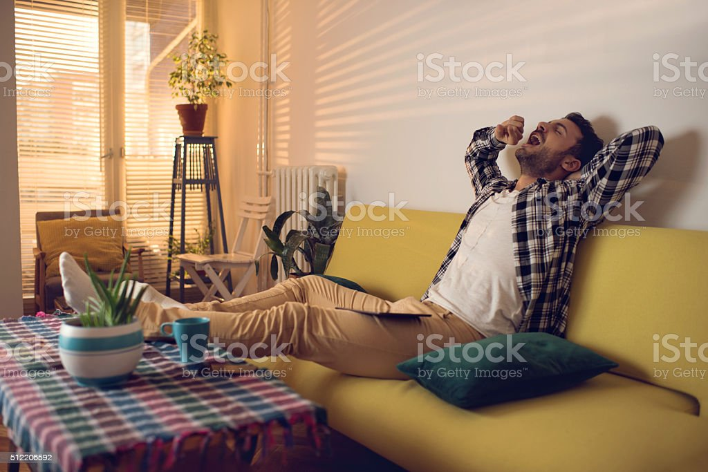 Tired young man yawning in the living room. stock photo