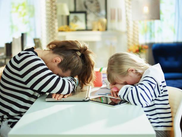 müde junge mutter und kind auf dem tisch liegen - homeschooling stock-fotos und bilder