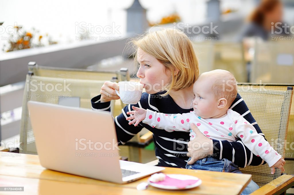 Tired young mother holding 6-month daughter and drinking coffee stock photo