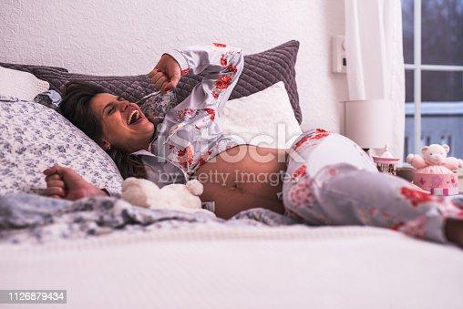Beautiful pregnant woman preparing for sleeping.