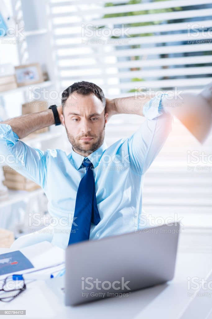 Tired young specialist feeling incapable to solve the necessary task stock photo