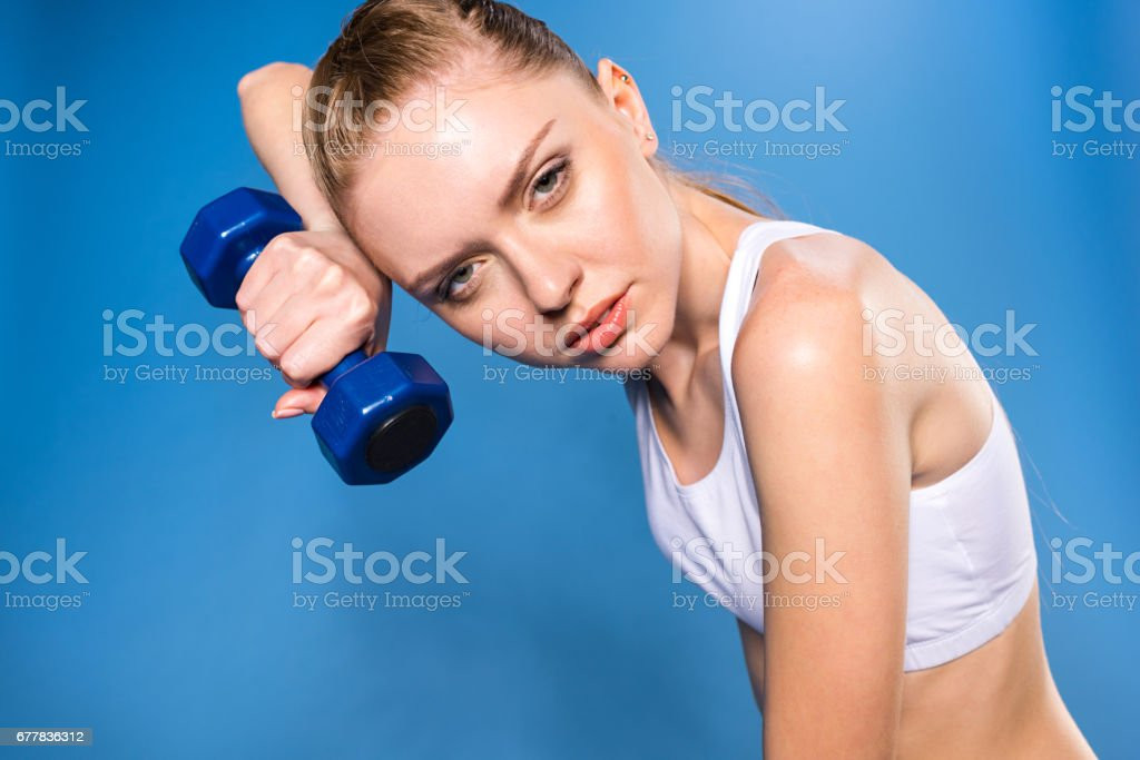 tired young sportswoman training with dumbbell isolated on blue in studio royalty-free stock photo