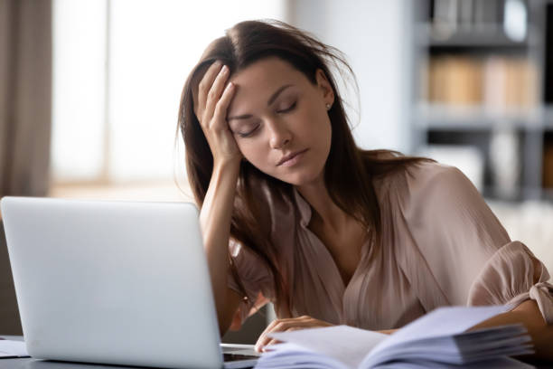 Tired young woman fall asleep working at laptop stock photo