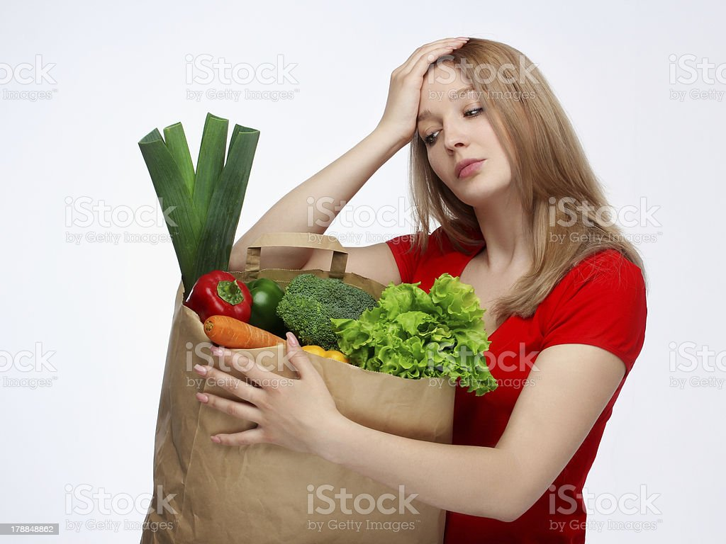 Tired young woman holding a paper shopping bag royalty-free stock photo
