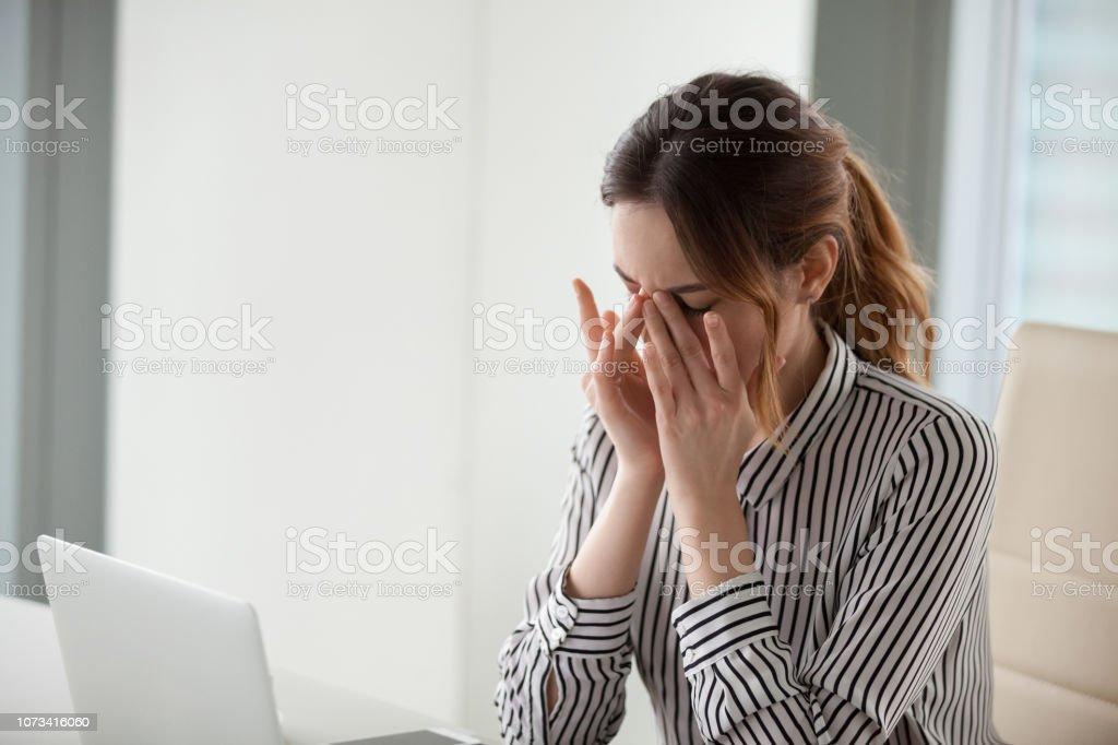 Müde junge Frau massiert Nasensteg am Arbeitsplatz – Foto
