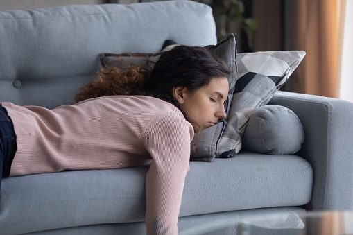 Exhausted young Caucasian woman lying on comfortable sofa in living room sleeping after hard-working day, tired millennial female fall asleep on couch at home, take nap or daydream, fatigue concept