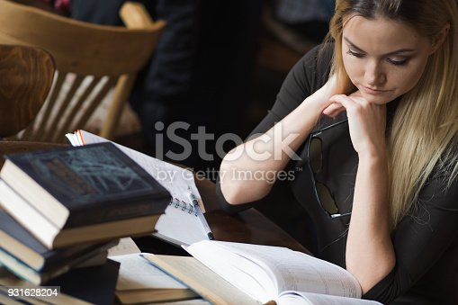 istock Tired young woman student of the University. Preparing exam and learning lessons in public library. 931628204