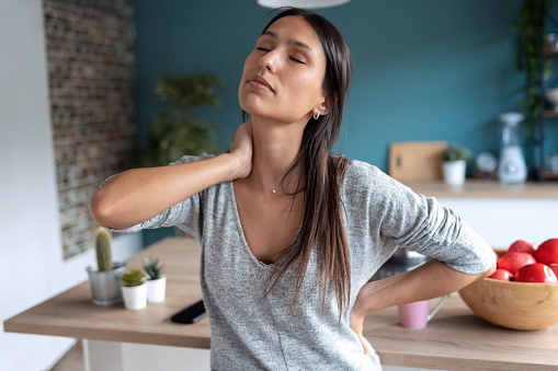 Shot of tired young woman suffering neck pain while sitting on the stool in the kitchen at home.