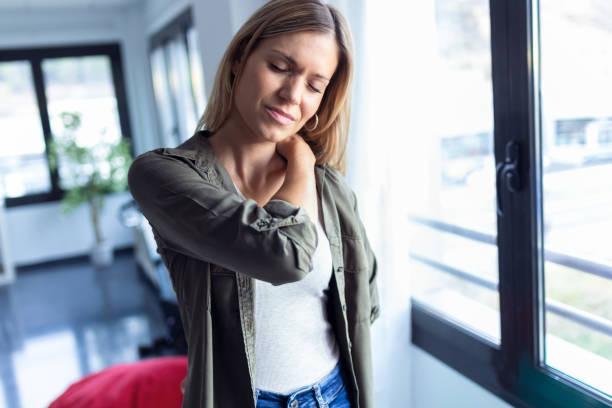 Müde junge Frau mit Nacken- und Rückenschmerzen im Wohnzimmer zu Hause stehend. – Foto