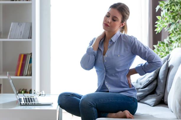 müde, junge frau mit schulter und rücken schmerzen sitzen auf der couch zu hause. - schultersteife stock-fotos und bilder