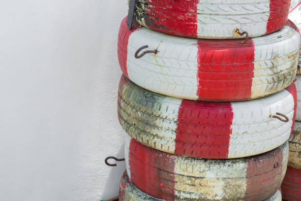 Tires alternately painted white and red stacked near the wall. Tires alternately painted white and red stacked near the wall. alternately stock pictures, royalty-free photos & images