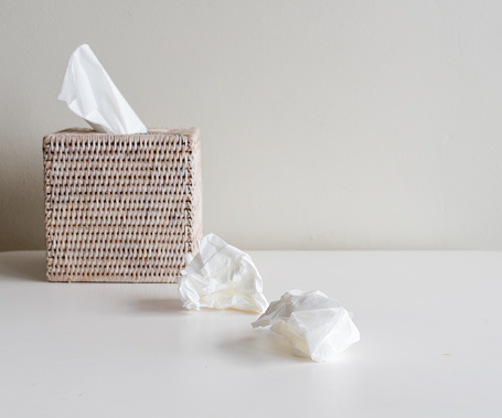 Rattan tissue box and crumpled tissues on table - cold and flu season concept, grief concept (selective focus)