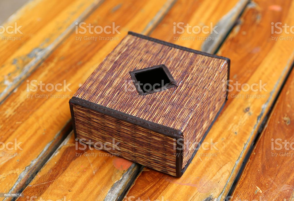 Tissue box of rattan basketry on wooden table stock photo