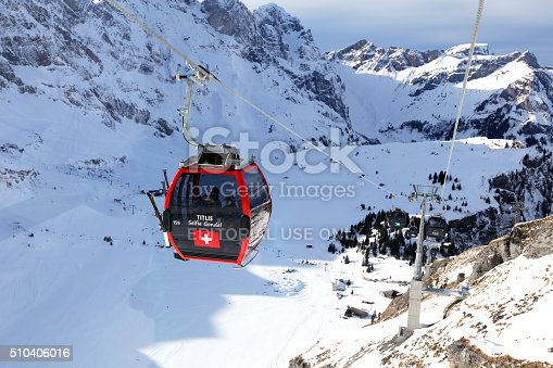 Engelberg, Switzerland - February 11, 2016: Titlis gondola with Swiss flag in Engelberg Switzerland. Mount Titlis (10,000 ft) is the highest glacier excursion destination and biggest ski and snowboard paradise in Central Switzerland attracting many skiers and tourists from all over the world.