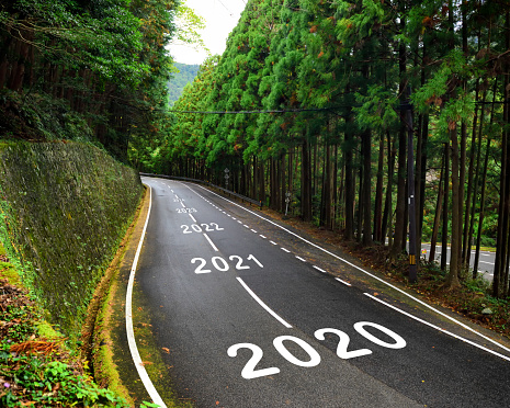 istock 2020 to 2043 on highway and white marking lines in the forest 1194402605