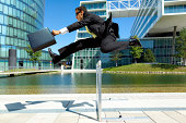 dynamic young business man with briefcase running over hurdle in urban surrounding