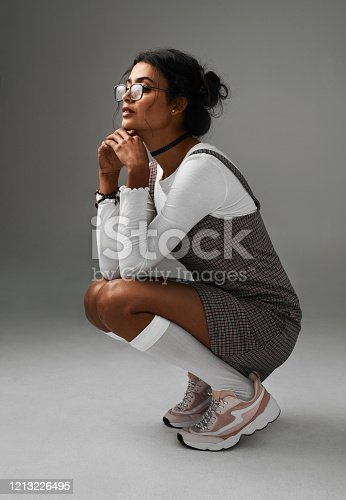 Studio shot of an attractive young woman crouching against a grey background