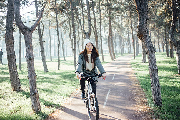 To bike or not to bike Women recreation in park on winter day, she ride a bicycle and enjoy in sunny day female biker resting stock pictures, royalty-free photos & images