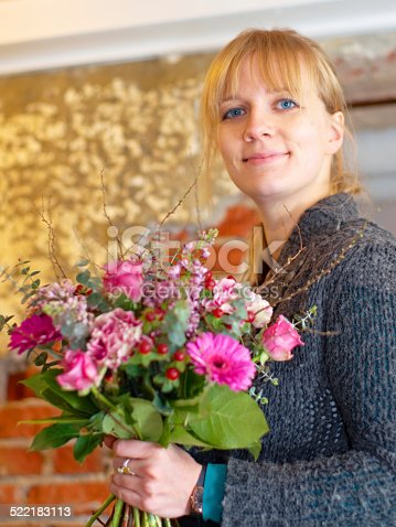 Portrait of a young woman holding a pretty bunch of flowers