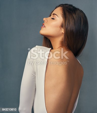 Studio shot of an attractive young woman posing against a grey background