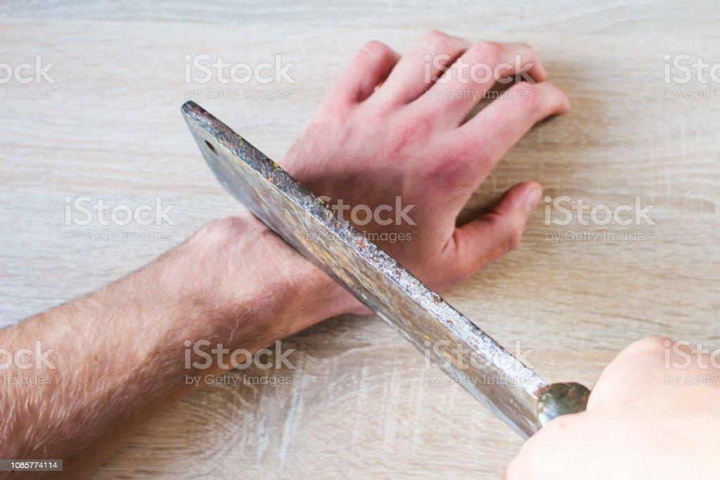 eine Hand mit einer Axt abzuschneiden – Foto